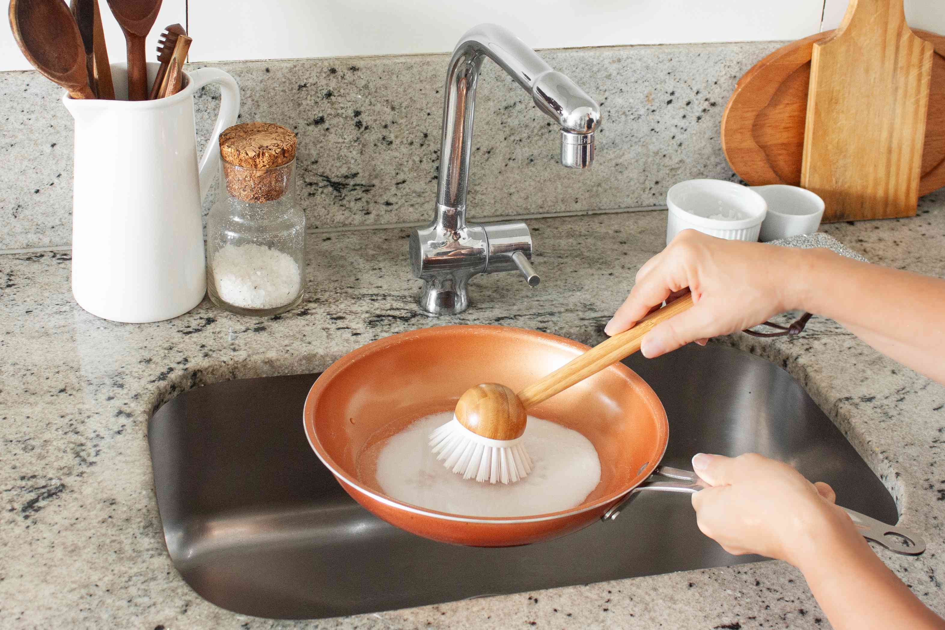 scrubbing the inside of the pan with a nylon bristle brush