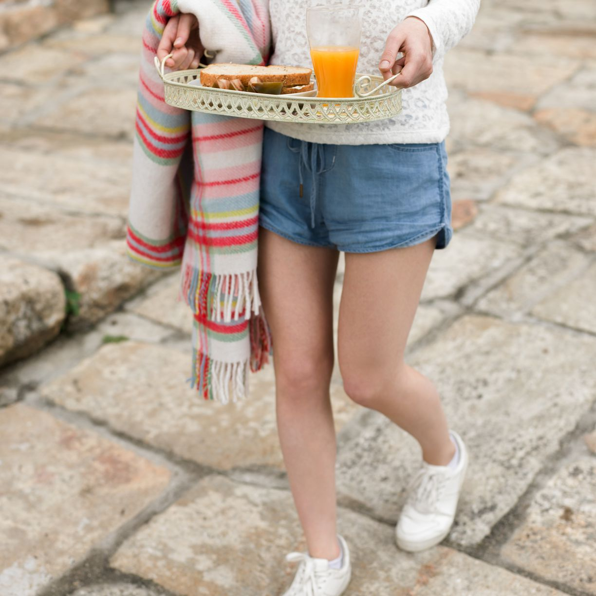 Girl with throw blanket and tray of food