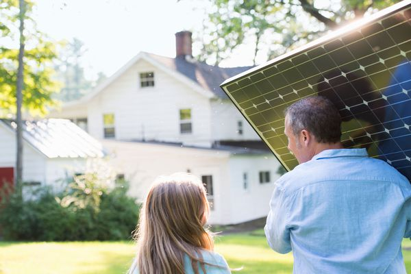 Man carrying a solar panel while walking next to his daughter