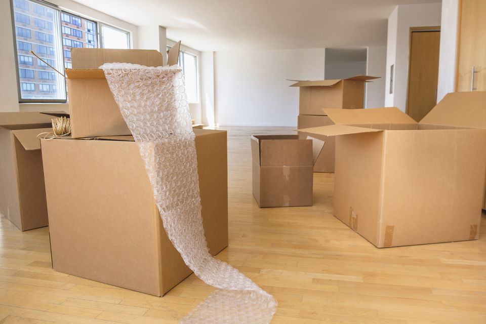 Cardboard boxes and bubble wrap in empty apartment