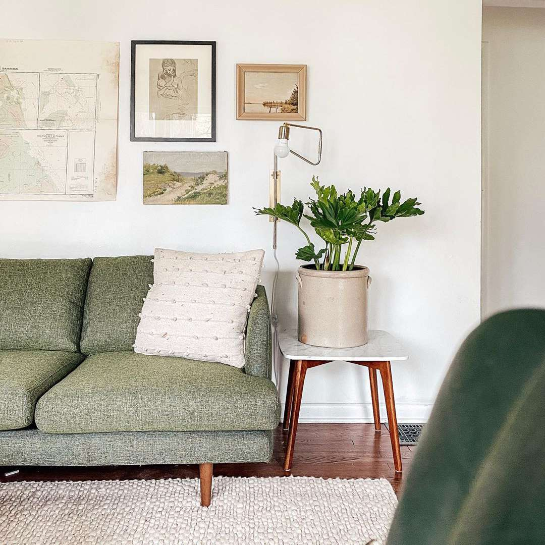 Living room with green couches and vintage pictures