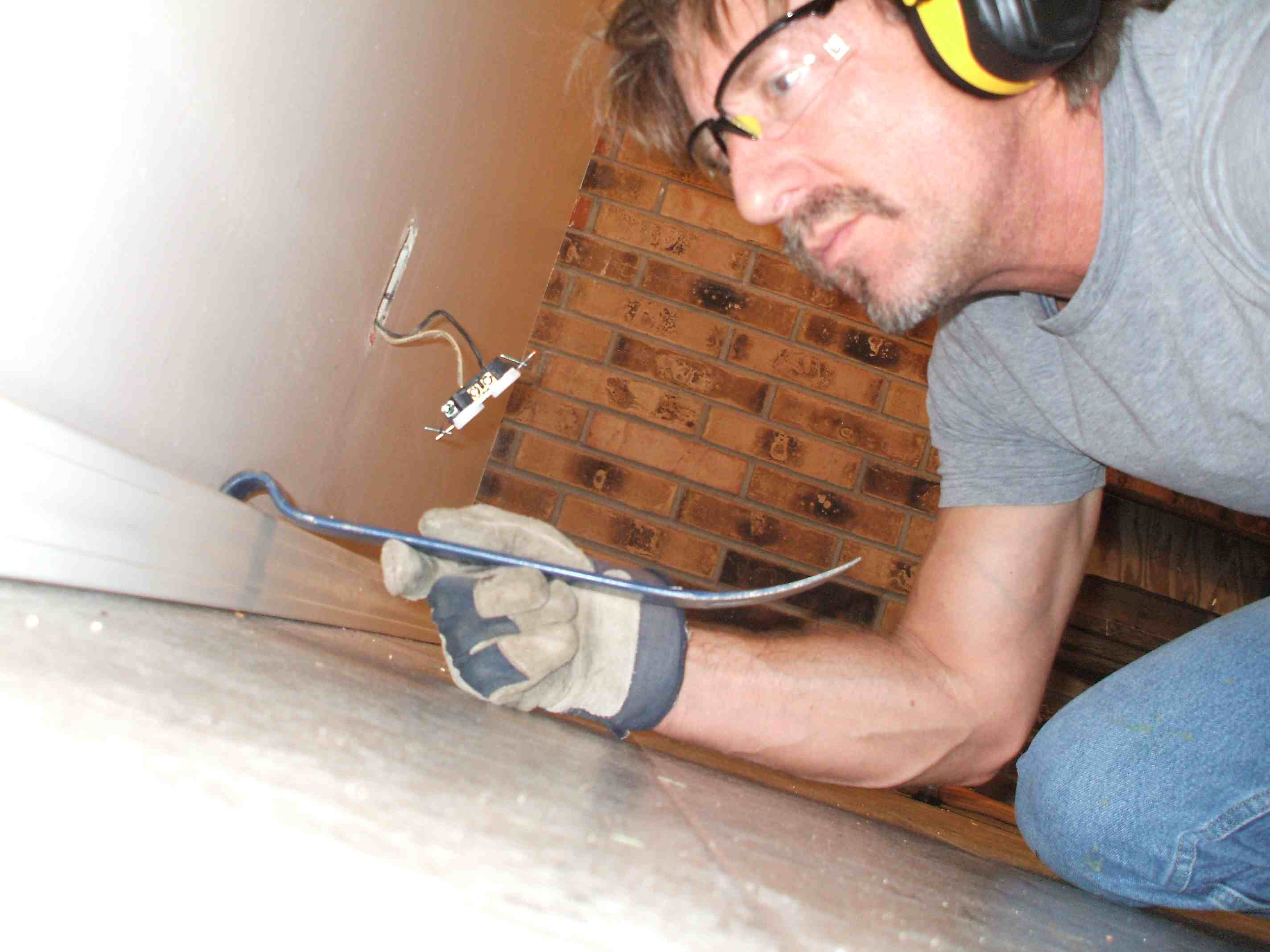 A man removing a wall's trim