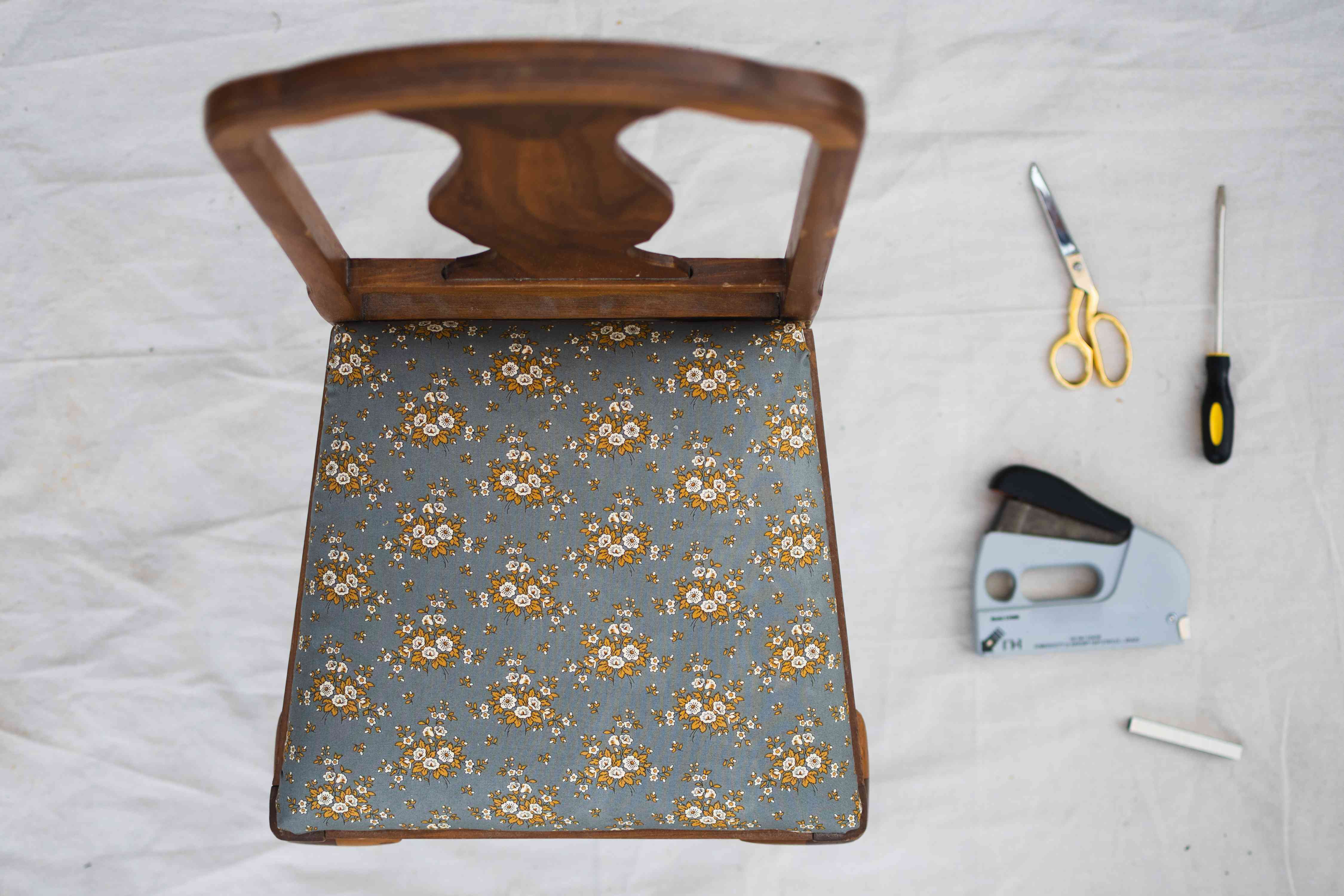 Chair seat reattached to wooden chair with new upholstered fabric next to materials and tools
