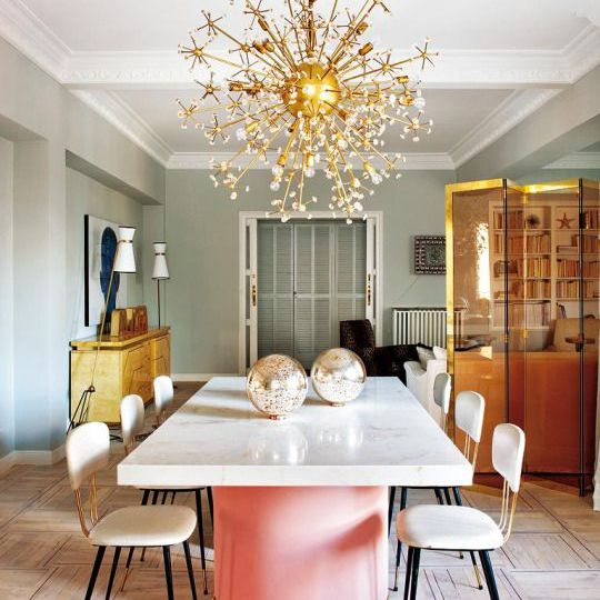 Gold chandelier and pink table in dining room