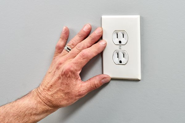 2 prong outlet with GFCI wiring touched by hand