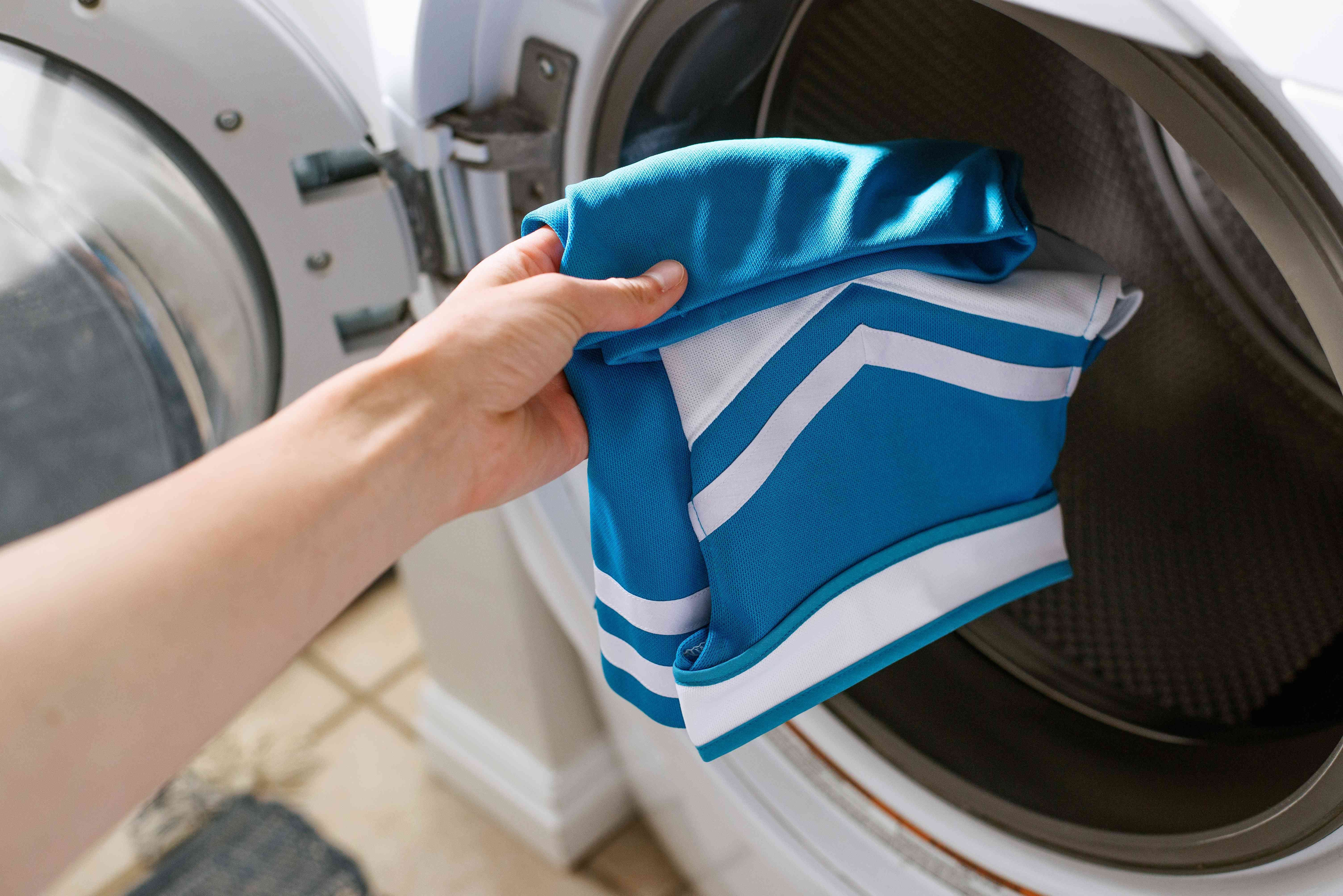 Blue and white cheerleading uniform top placed in washing machine alone