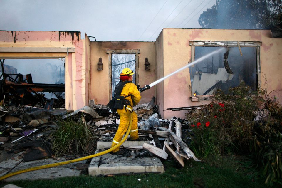 Firefighter putting out a fire in a house