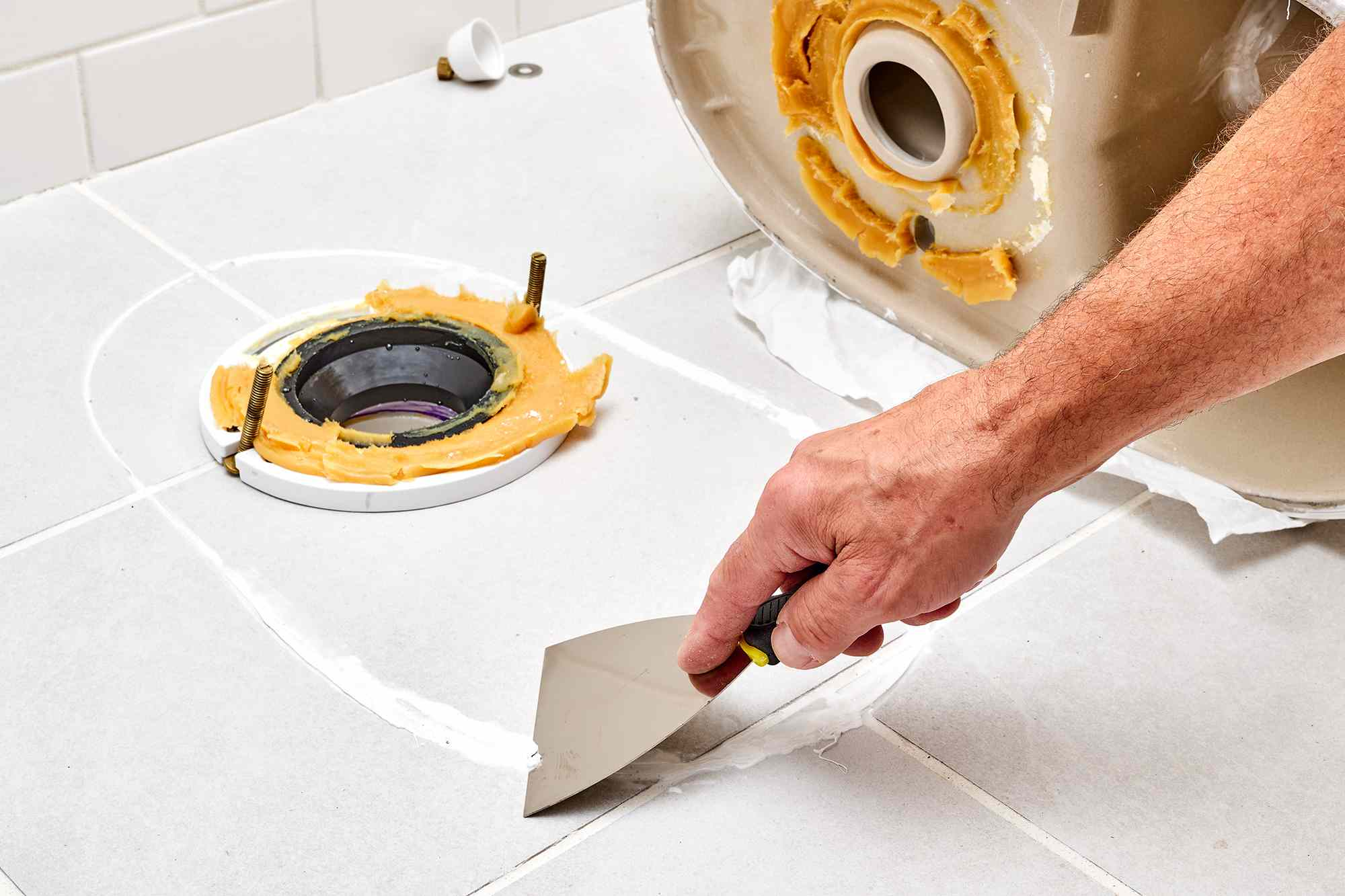 Putty knife removing old caulk from floor