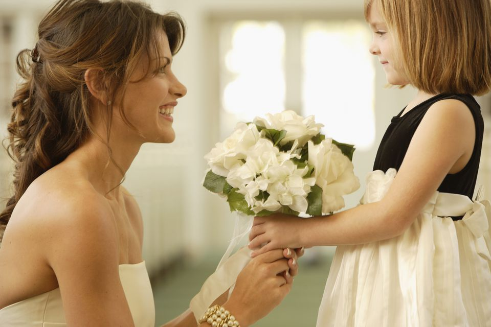 Bride handing bouquet to flower girl