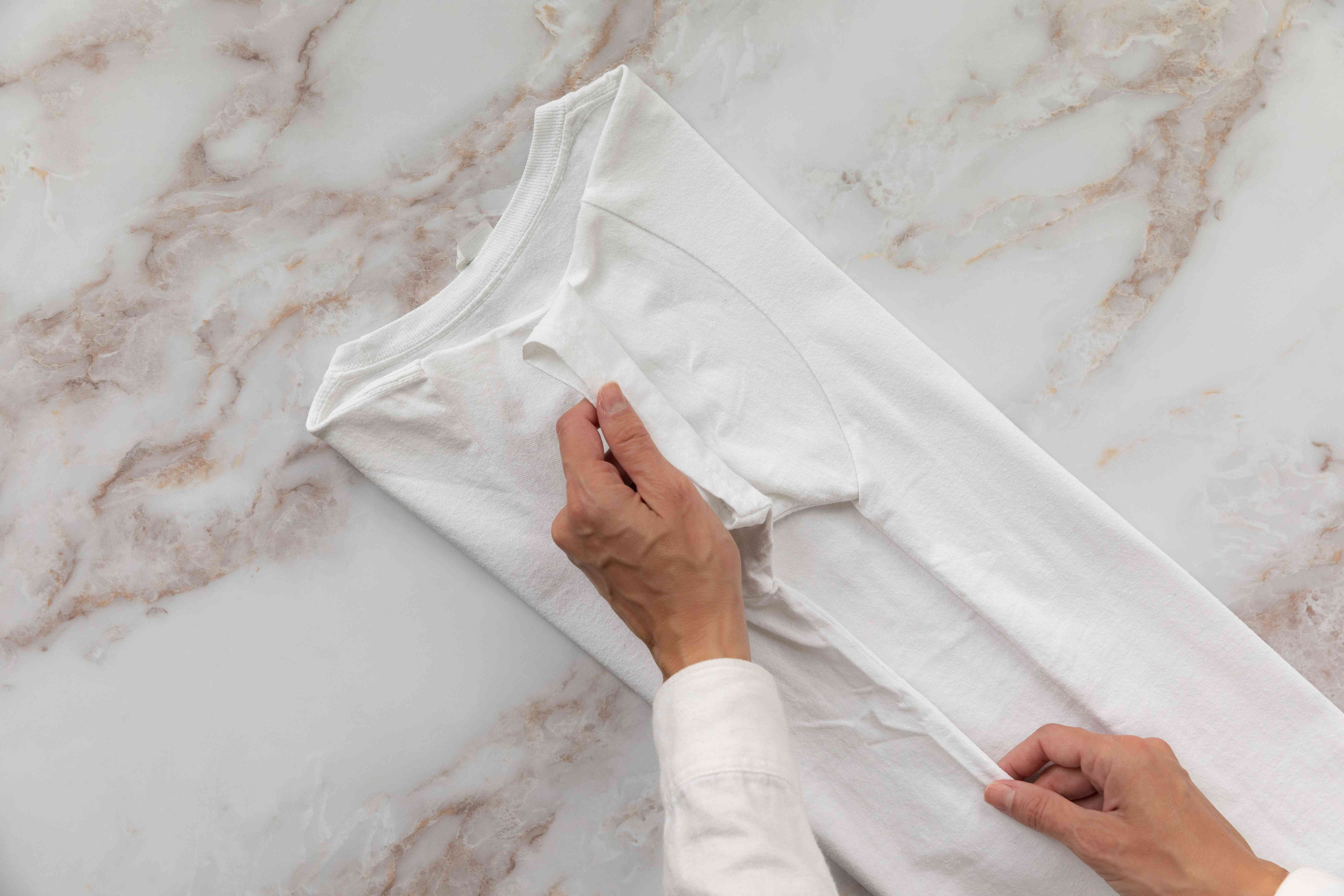 White t-shirt facing down and folded in thirds