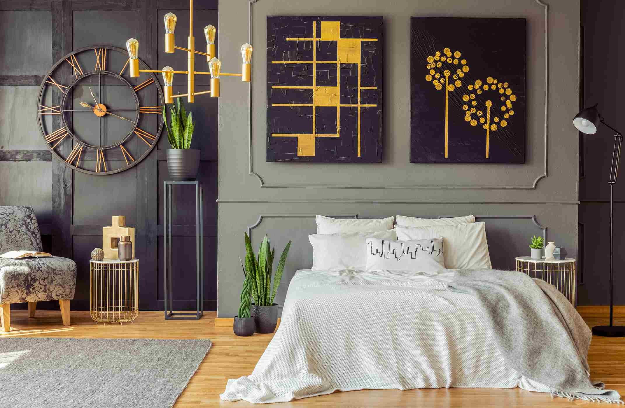 Grey blanket on bed against the wall with black posters in bedroom interior with clock.