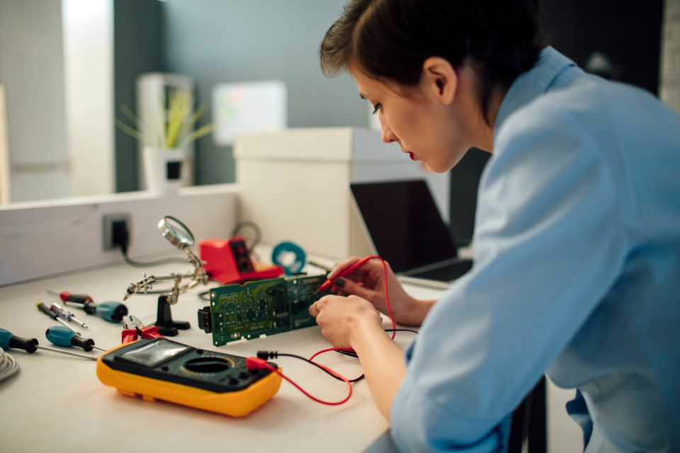 Woman Testing circuit board in her office.