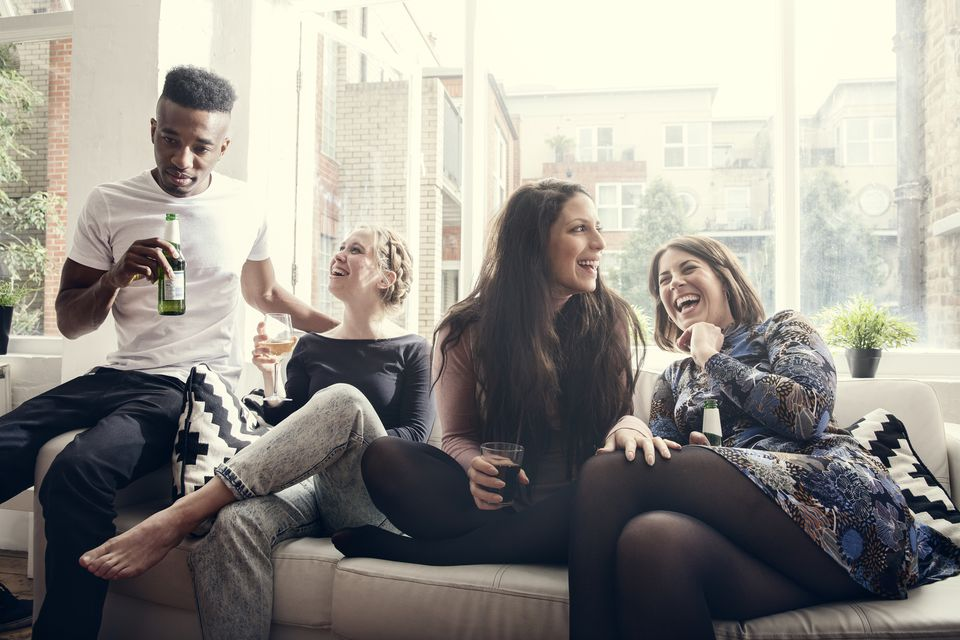 Friends laughing while sitting on a couch at a party