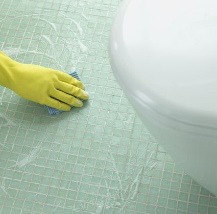 Hand in a Rubber Glove Cleaning a Tiled Floor in a Bathroom