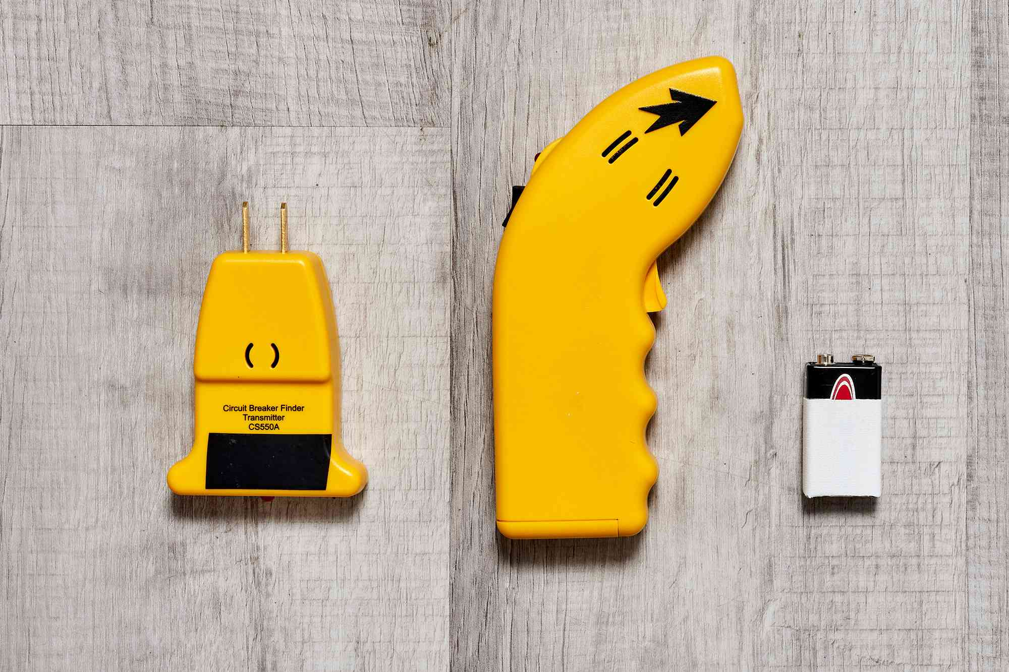 Circuit breaker finder and 9-volt battery on wooden surface