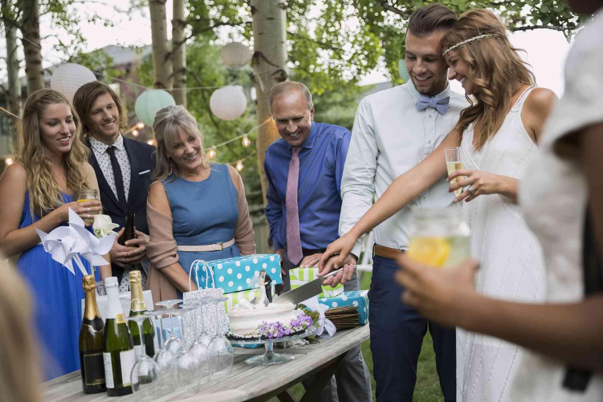 Novia y novio cortando pastel en la recepción de la boda