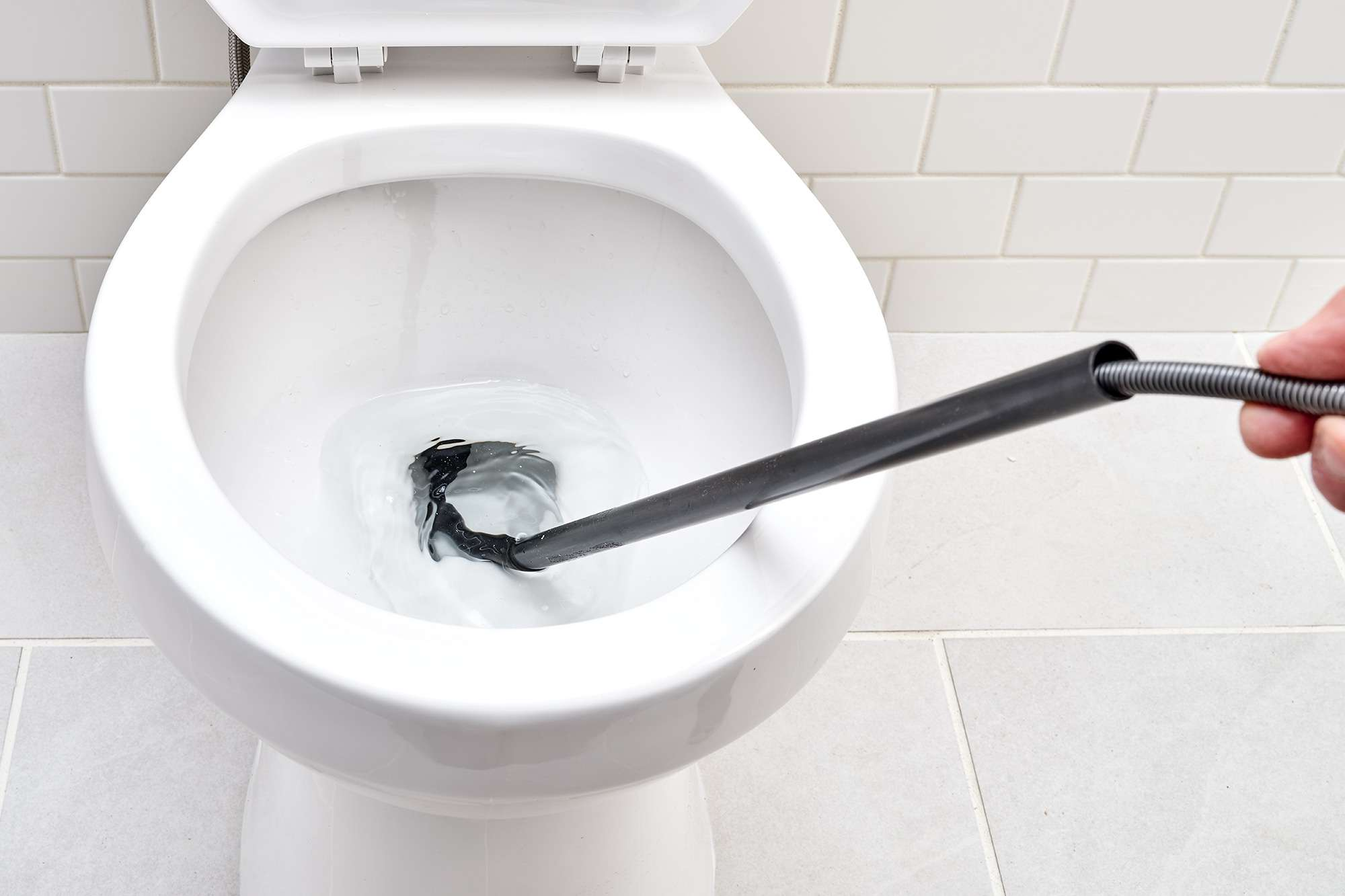 Cable extended on toilet auger to move through trap bends