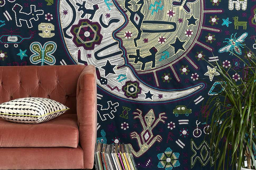 Wall tapestry with a moon hung next to a mauve couch