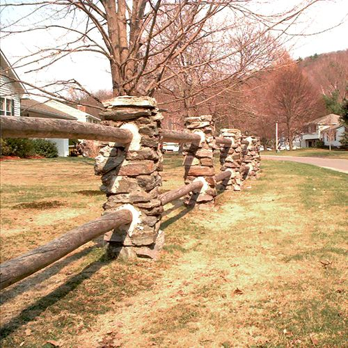 Picture of log fence with stone columns.