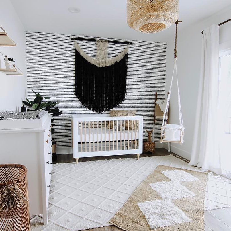 Black, white, and boho nursery with dramatic wall hanging focal piece