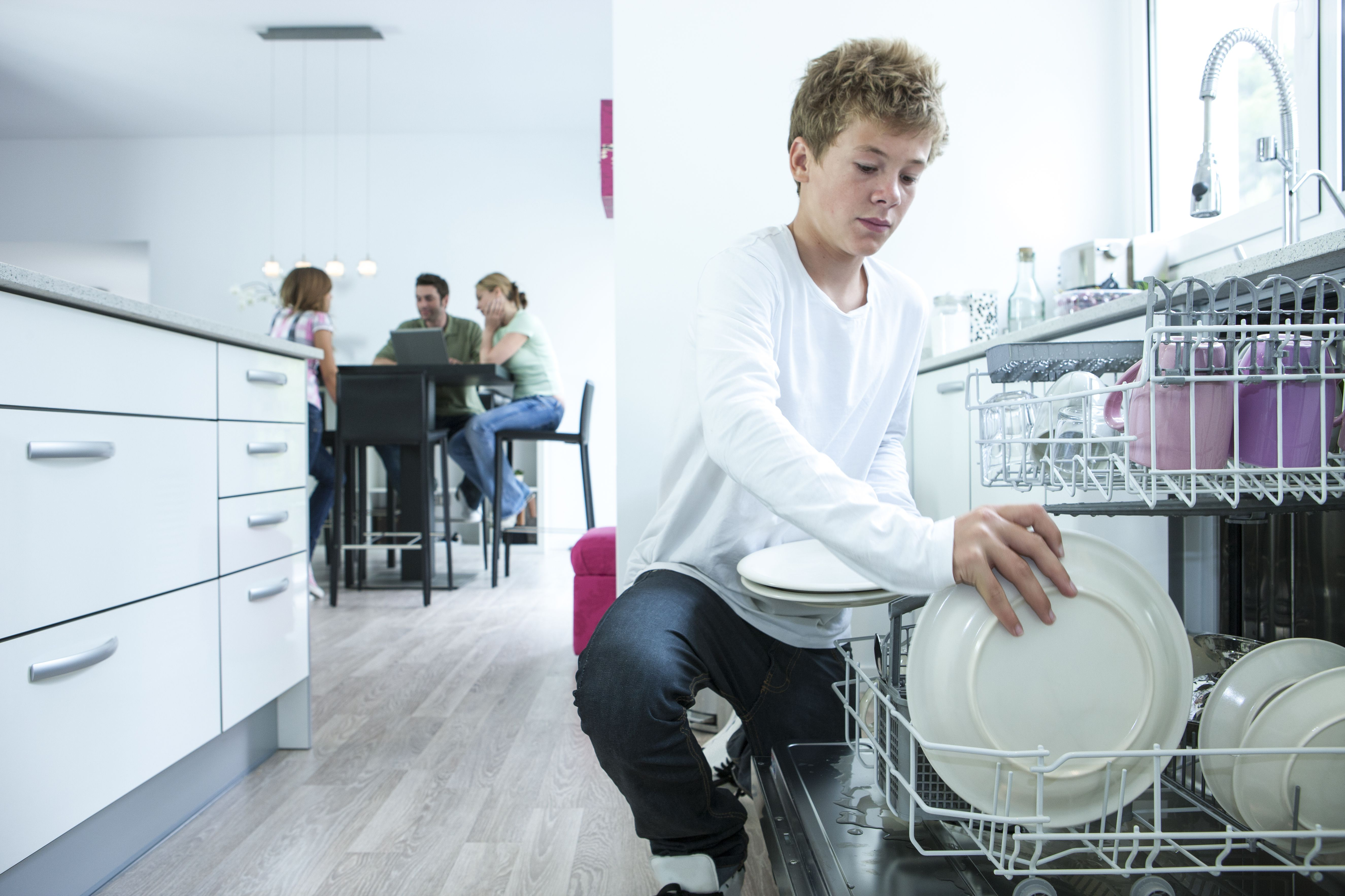 Teenage boy removing plates from dishwasher in kitchen