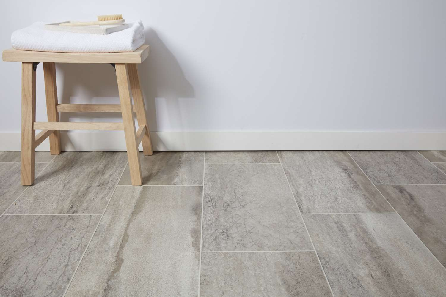 Sheet vinyl flooring with wooden stool and white folded towel