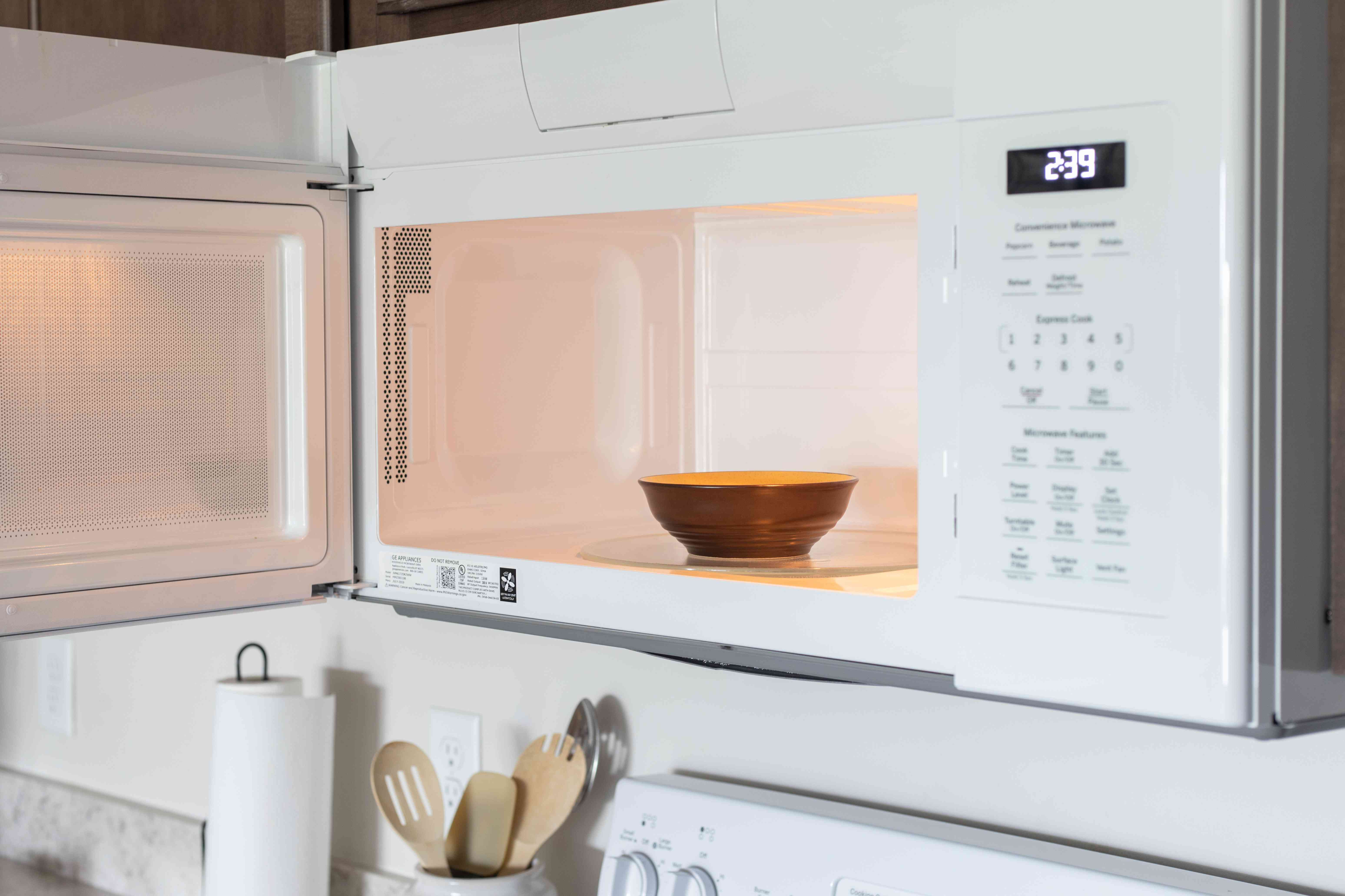Microwave door open with bowl sitting inside
