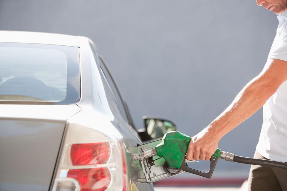 A man pumping gas into a car