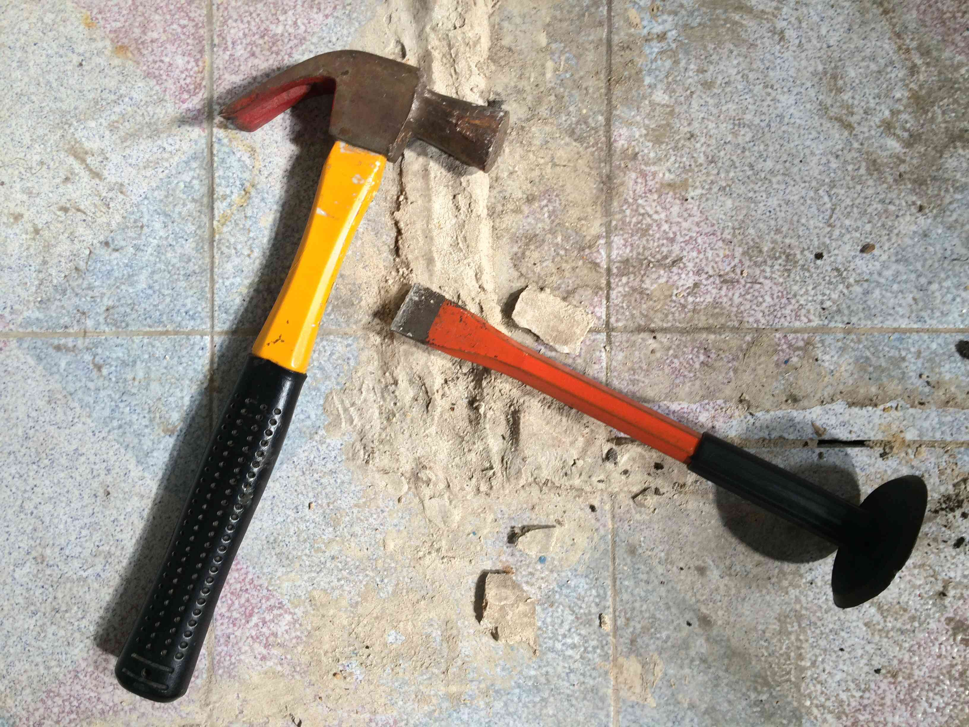 Hammer and chisel on tile floor