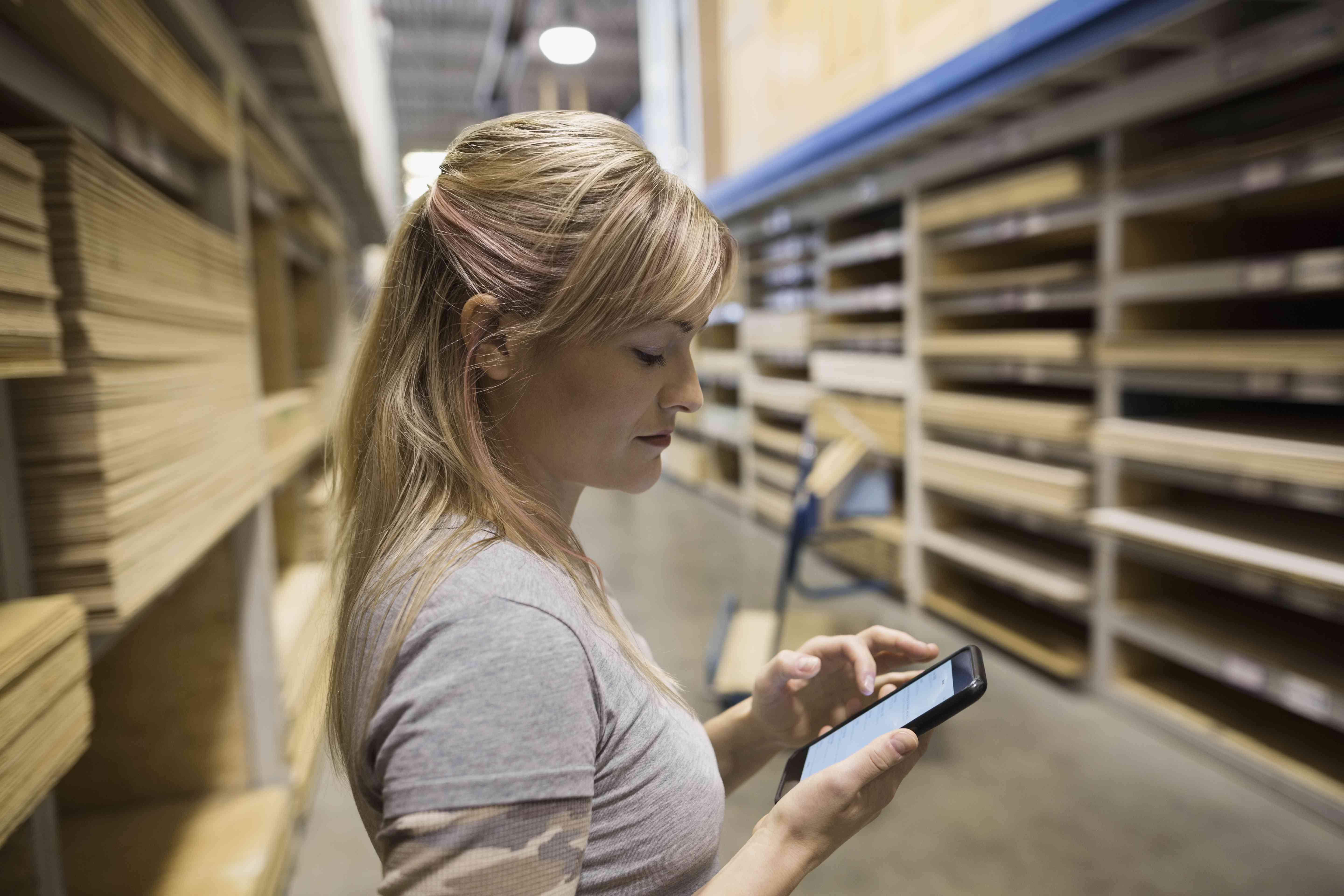 Woman with cell phone shopping for plywood in home improvement store
