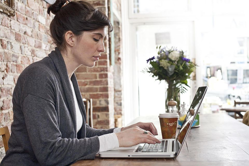 Girl using laptop computer in cafe