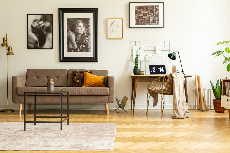Framed photos gallery on a white wall of a hipster living room interior and workspace with laptop on a wooden desk