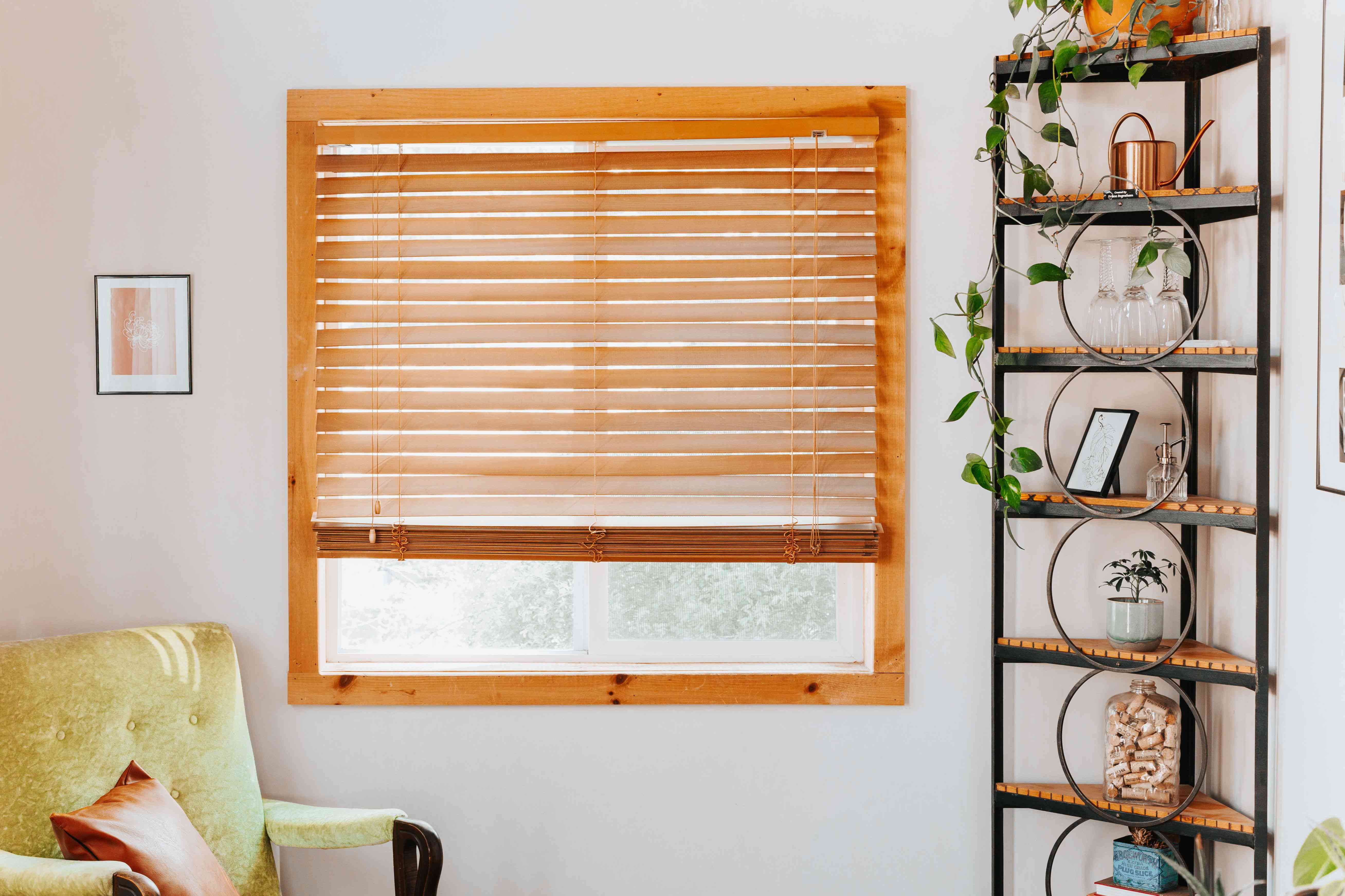 Wooden window blinds next to yellow chair and corner shelving with plants and decor items