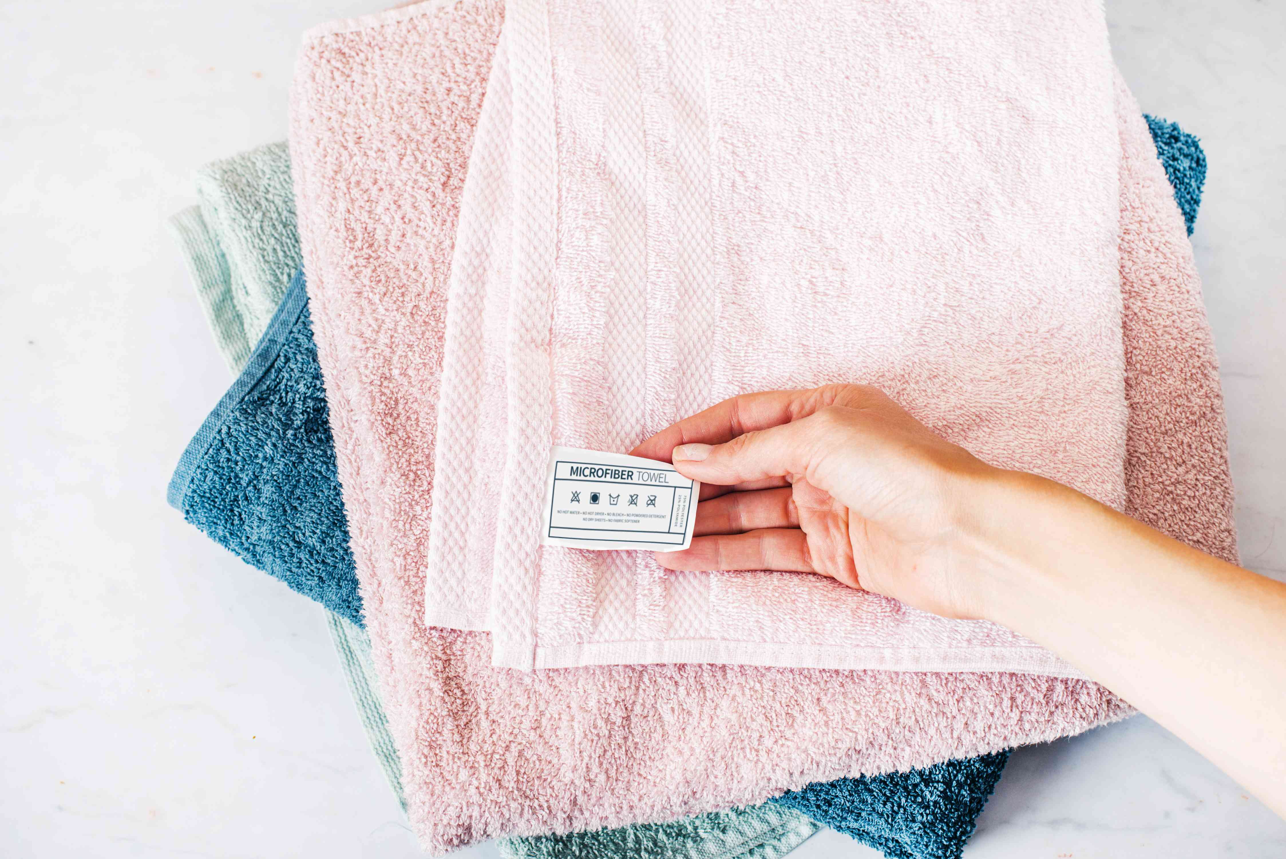 Light pink, blue and green microfiber towels stacked on each other with care label held by hand