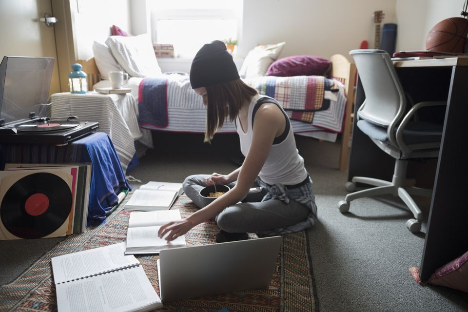 Female college student studying on floor in dorm room