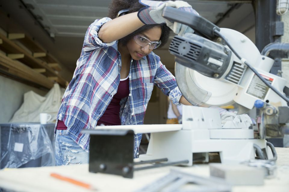 Focused woman using table saw for home improvement project in garage
