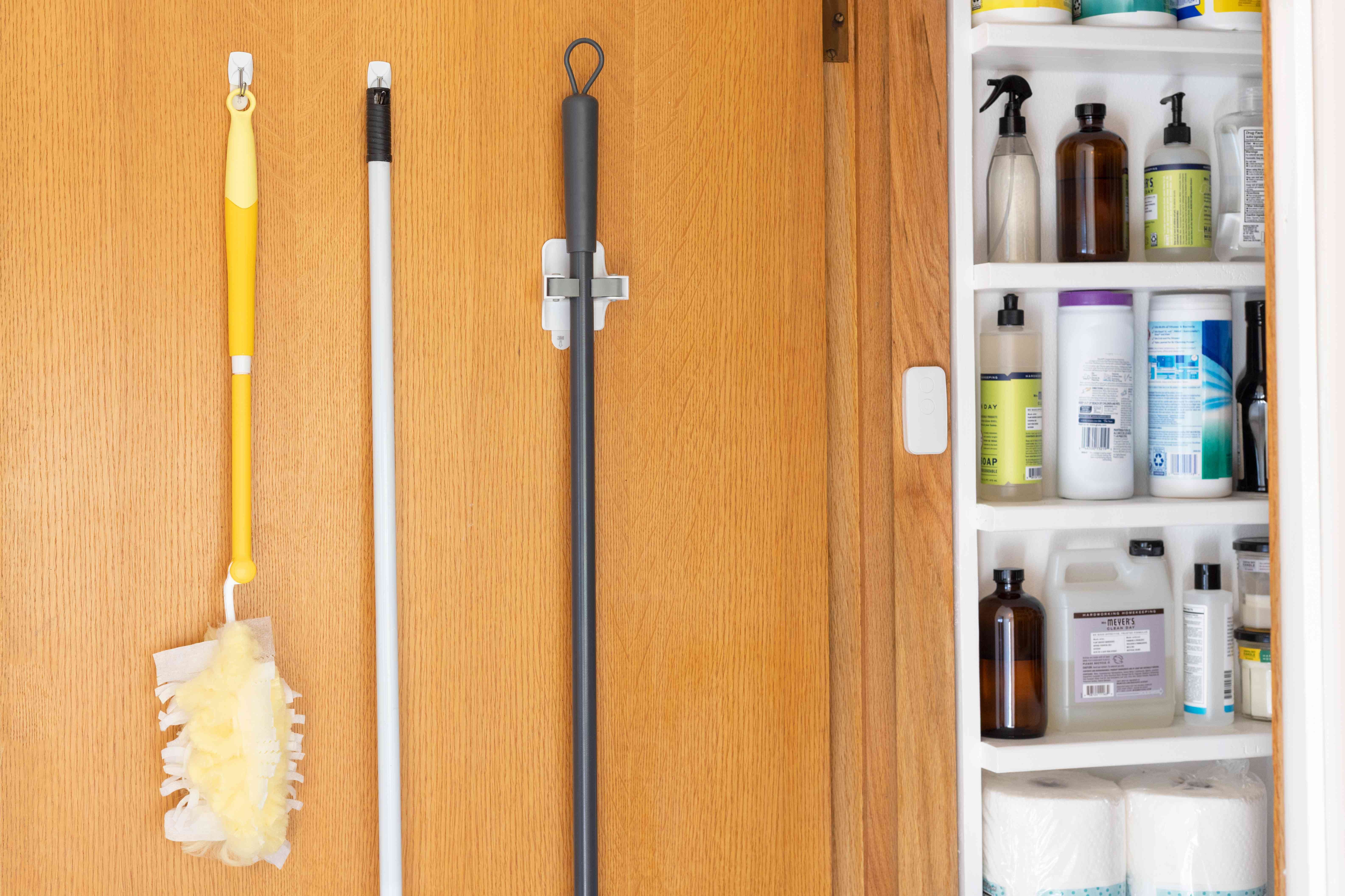 Broom and dust brush handles hanging vertically on door for storing