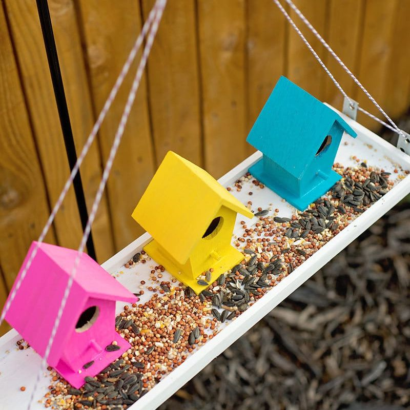 A pink, yellow, and blue bird feeder with bird houses
