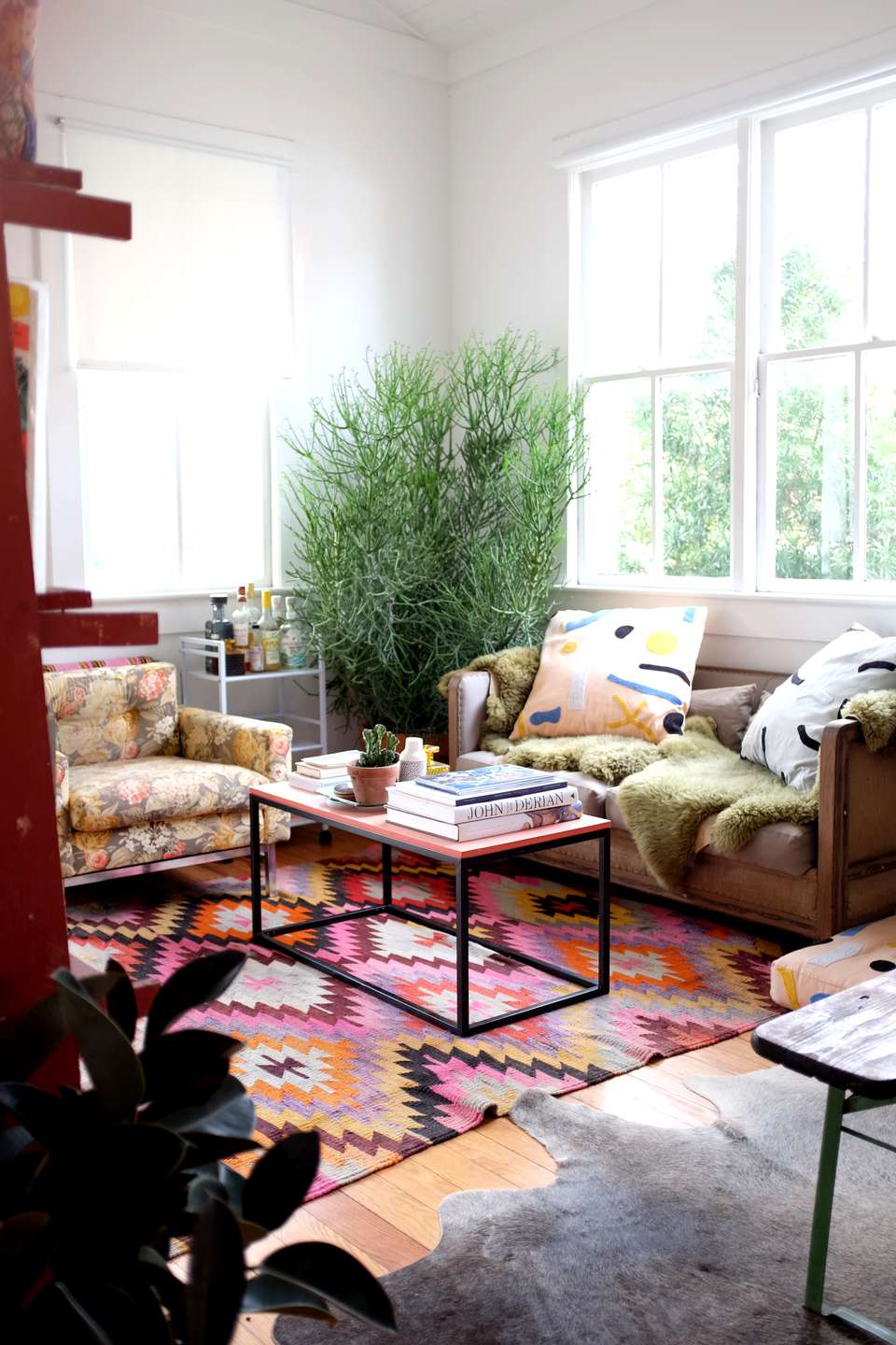 Modern bohemian room with plants and geometric rug