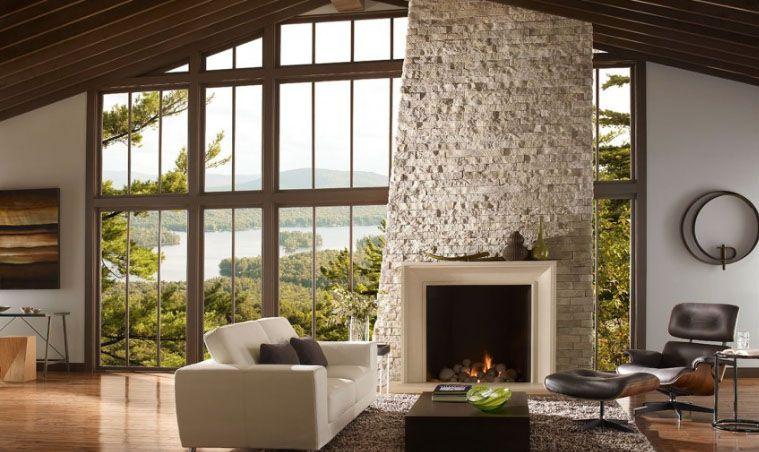 Revestimiento de chimenea de piedra seca apilada contra ventanas de piso a techo y un sofá blanco