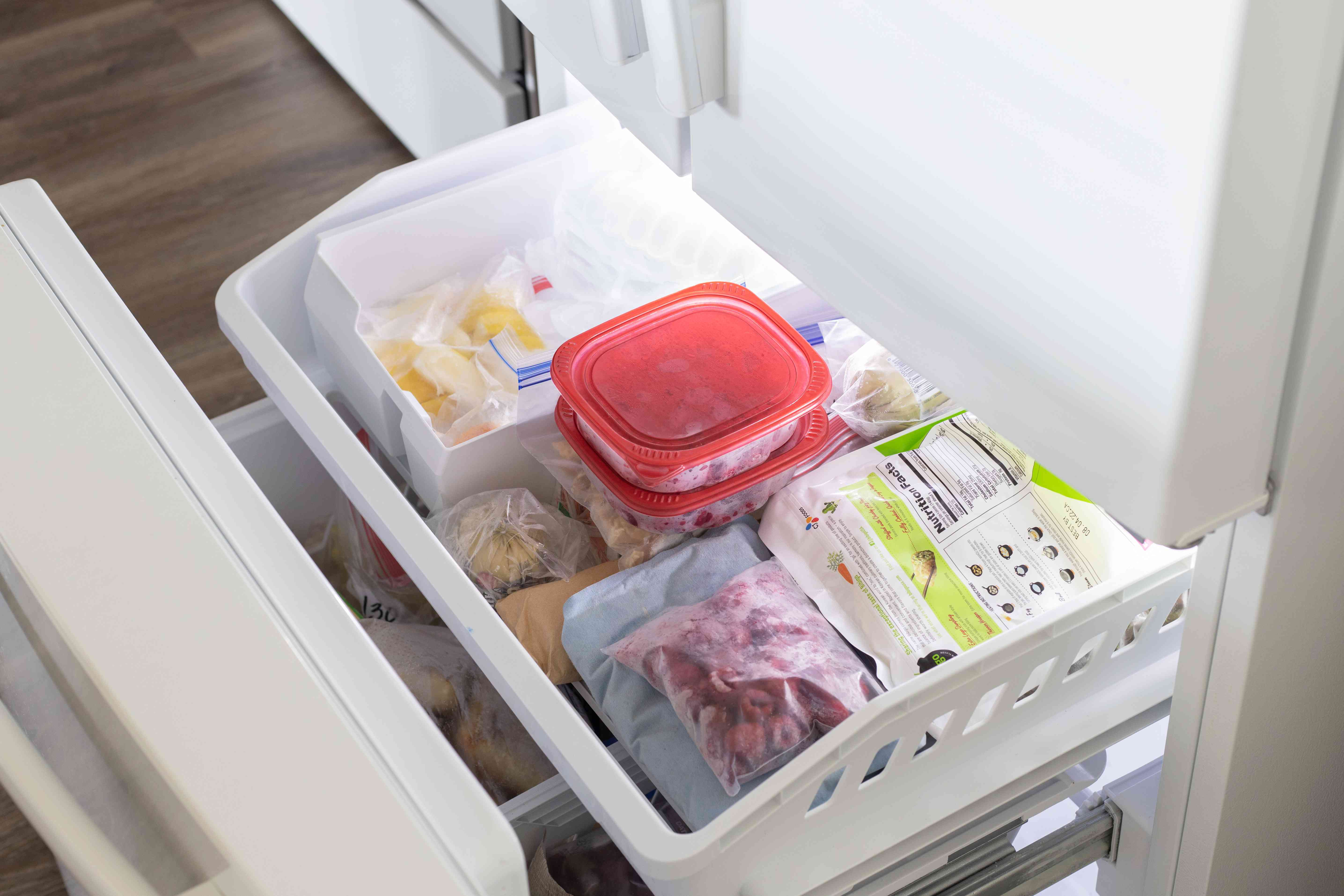 Freezer full of frozen foods and containers to lower electric bill