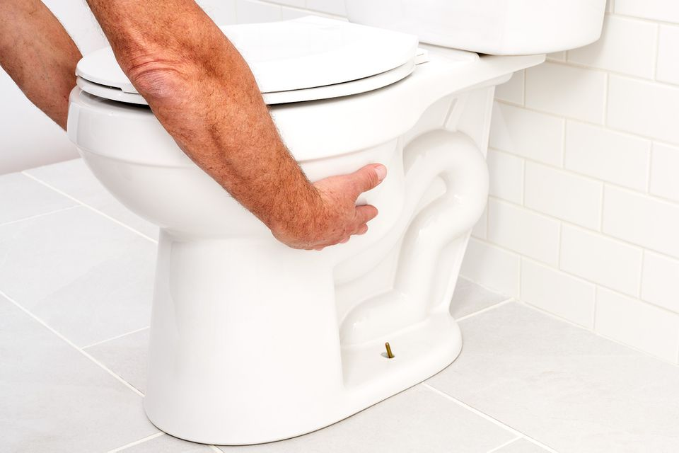 Bathroom toilet being moved while holding bowl on both sides