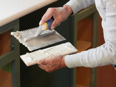 White tile mastic being scraped and applied to back of tile by hand