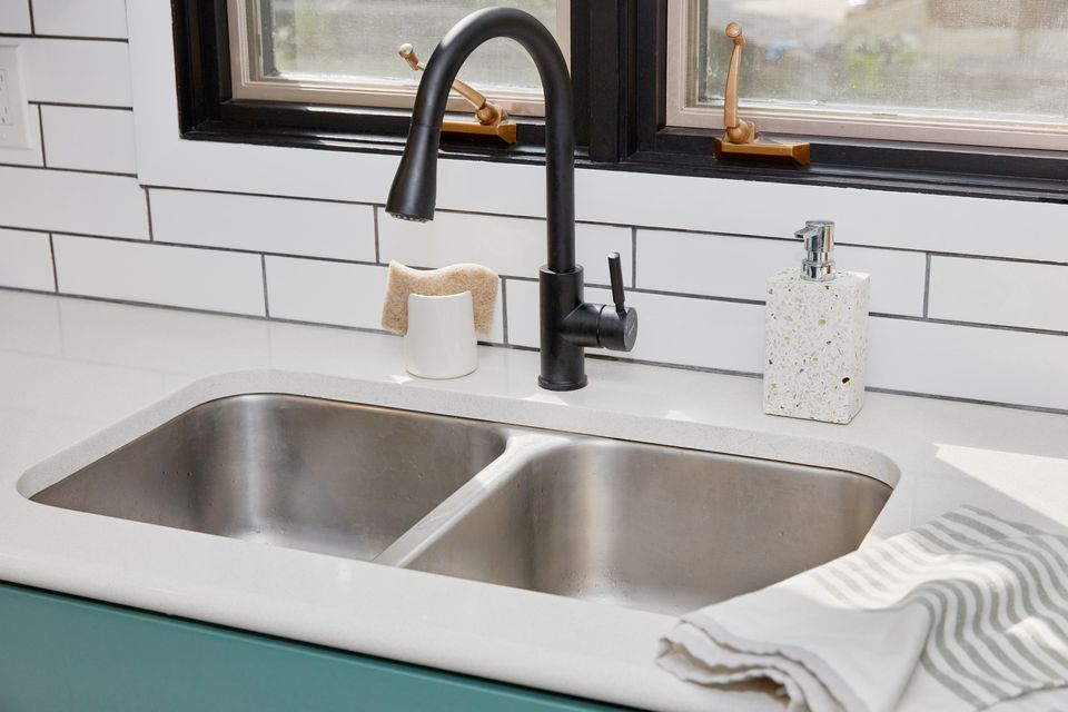 Low-divide kitchen sink with black faucet and white countertops next to window