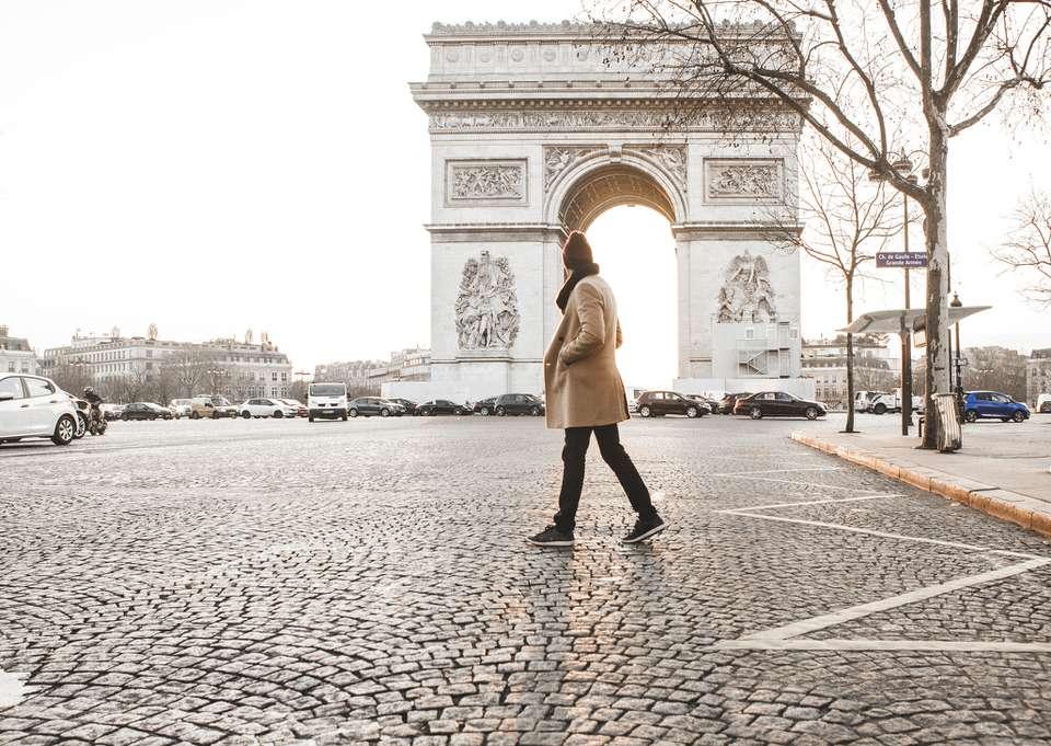 Man walking in front of Arc de Triomphe