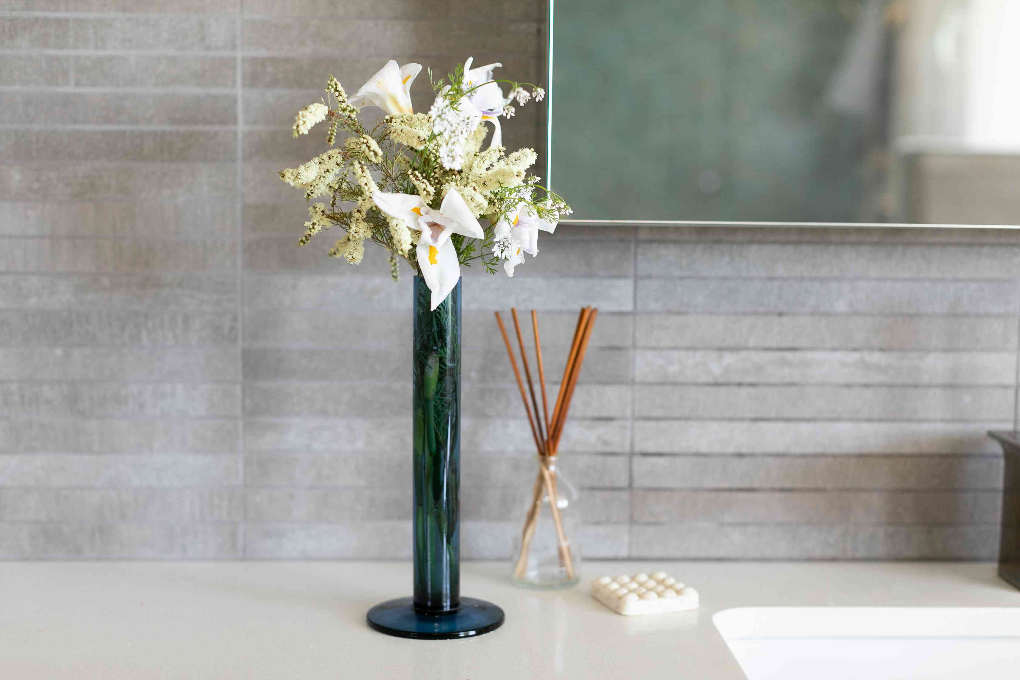 Reed diffuser next to massage soap bar and vase with flowers in guest bathroom