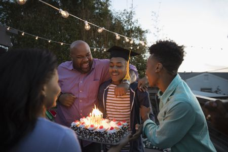 2d2776b333f African American family celebrating graduation with cake on summer deck