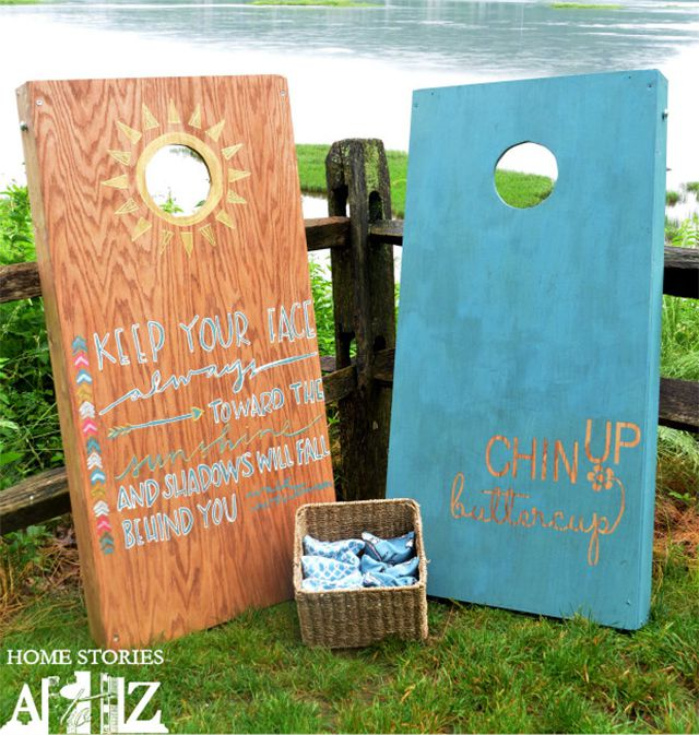 Two blue cornhole boards sitting by a fence