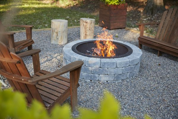 Fire pit with light gray stones surrounded by wooden chairs and fire
