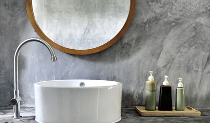 Concrete vanity with a white porcelain sink, a wood circular mirror, and soaps.